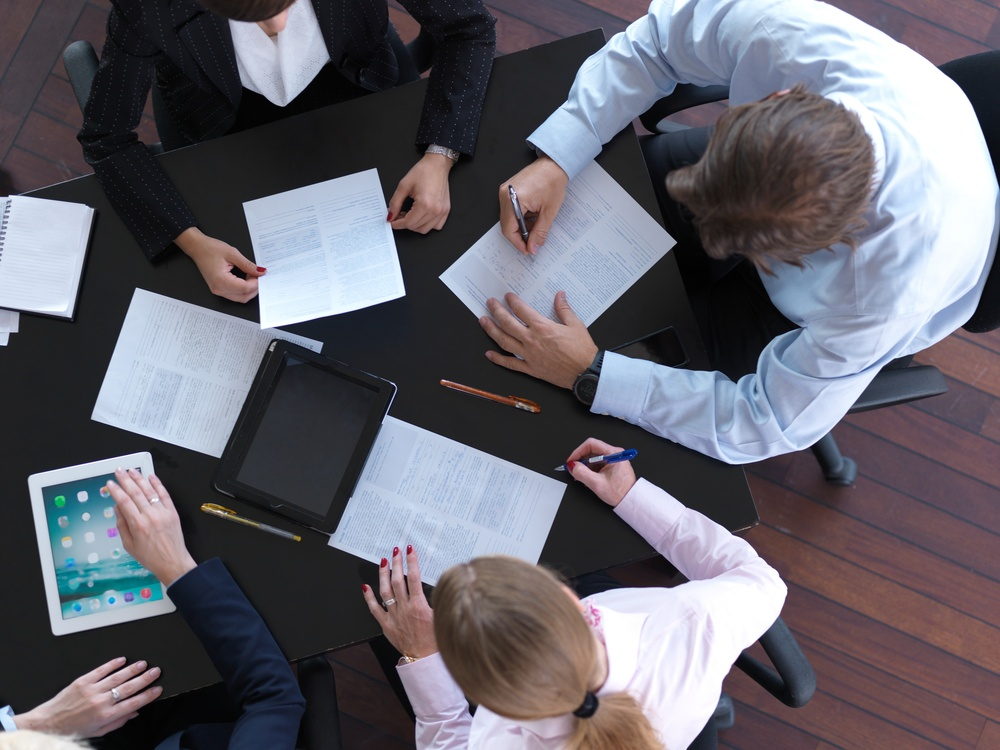 top view of  business people group on meeting, working in modern bright office indoor with tablet computer.jpeg